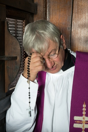 confess: Vicar or priest sitting in a confession booth and listening to sins
