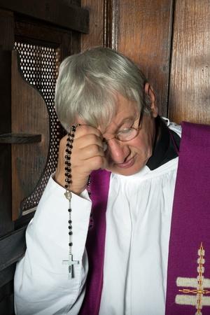 religion catolica: Vicario o sacerdote sentado en un confesionario y escuchar a los pecados Foto de archivo