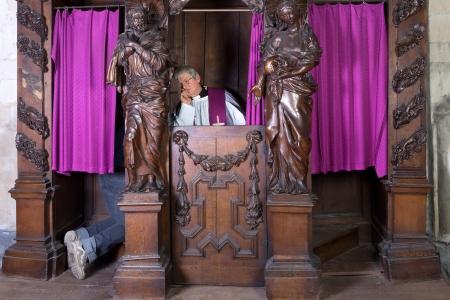 Voeten van een persoon in een bekentenis stand en de priester luisteren (opgenomen in een middeleeuwse 17e-eeuwse kerk)