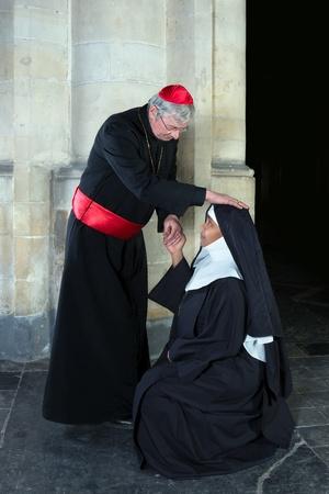 sotana: Monja Rodillas saludando a un cardenal en una iglesia medieval Foto de archivo