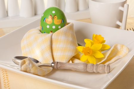 kept: Easter egg kept warm with a folded yellow napkin on a breakfast table