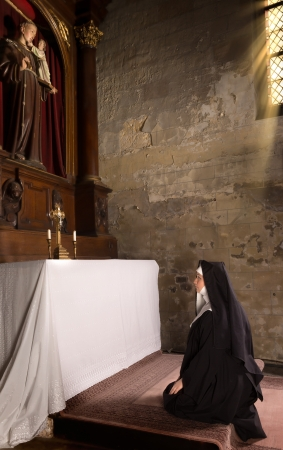 christian altar: 17th century church interior and a nun in prayer at the altar Stock Photo