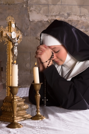 Closeup of an altar of a medieval 17th century church and a young nun in prayer