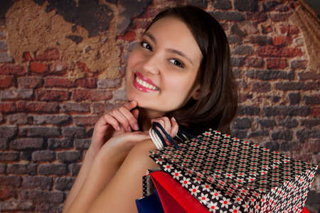 Attractive happy woman with shopping bags waving her hand photo