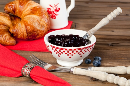 napkin ring: Wooden table with croissants, red napkins and antique silver napkin ring