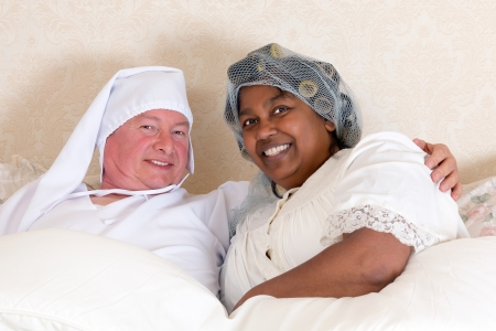 Mature couple in vintage clothing smiling in bed photo