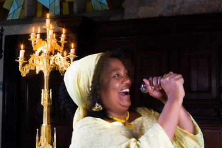 Happy gospel singer with microphone singing during mass Stock Photo - 18237732