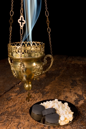 Frankincense: Smoking incense thurible and a golden plate with franincense and charcoal pieces