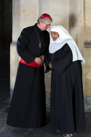 roman catholic: Nun and Cardinal talking against a background of an old pillar in a medieval church