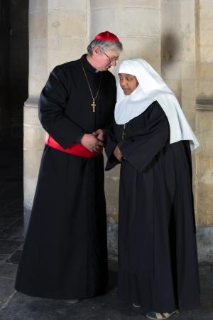sotana: Nun y el cardenal habla sobre un fondo de un pilar de edad en una iglesia medieval
