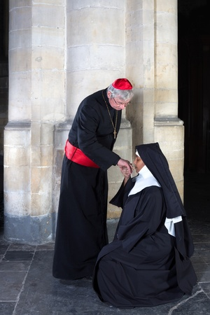 Mature nun kissing the ring of a cardinal in a medieval church photo