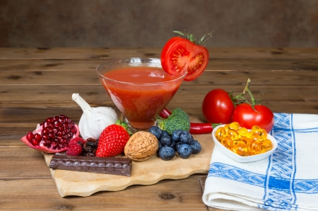 Wooden table and a small tray filled with antioxidants fruits and vegetables photo