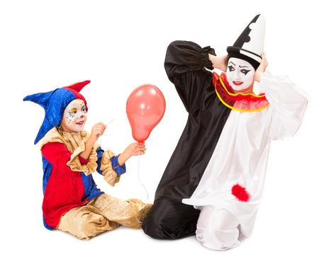 pierrot: Little clown girl scaring a pierrot by making a balloon explode Stock Photo