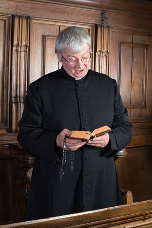 hymn: Vintage victor dressed in black cassock singing a hymn Stock Photo