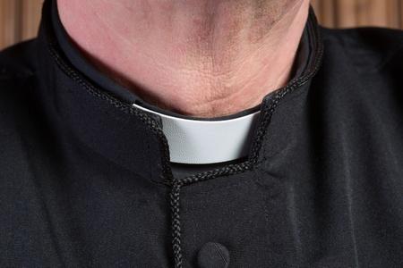 collarin: Primer plano del cuello de un sacerdote que llevaba una camisa de color negro con sotana y alzacuellos blanco