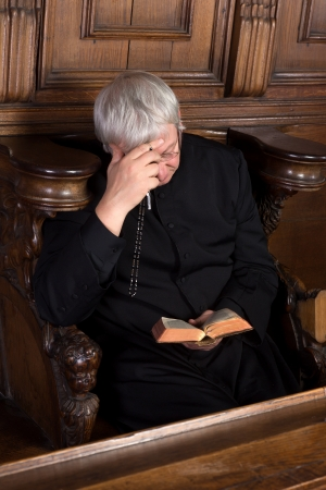 cassock: Vintage priest dressed in black cassock reading and holding a rosary