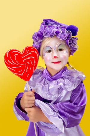 harlequin clown in disguise: Lovely clown girl holding a heart shape lollipop for valentines day