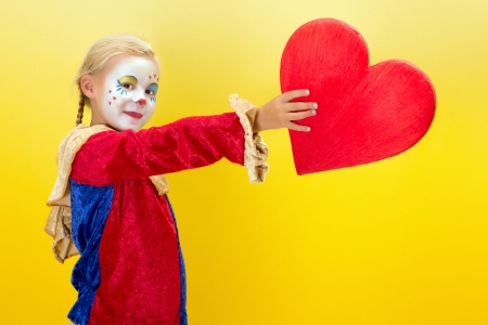 harlequin clown in disguise: Cute girl clown giving a red heart for valentine or mothers day