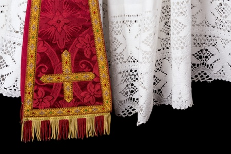 catholic mass: Closeup of a red vestment set of maniple and white lace priest surplice