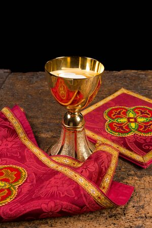 Red damask vestment set of burse and chalice veil, plus chalice filled with holy wafers or hosts photo