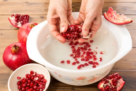 tannins: Hands seeding a pomegranate with the water method Stock Photo
