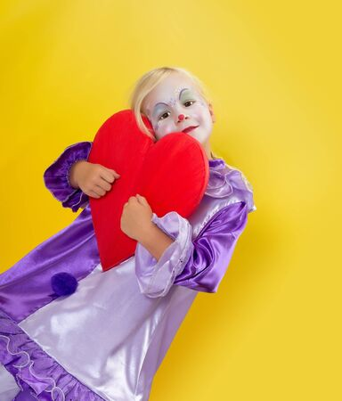harlequin clown in disguise: Adorable young girl clown holding a red heart for mothers day
