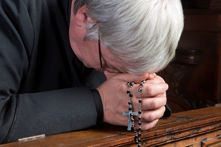 Humble priest kneeling down and praying with his rosary Stock Photo