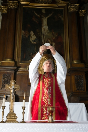 holy eucharist: Catholic mass with moment of consecration by a priest in a medieval church with 17th century antique interior  including the painting