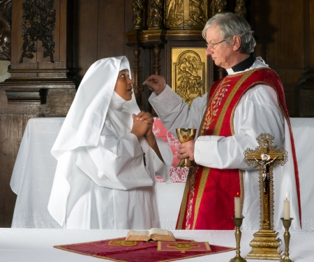 religious service: Catholic priest giving holy communion to a nun