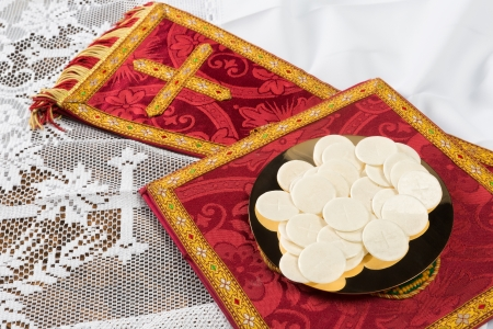 mass: Red vestment set and communion hosts on a golden plate Stock Photo