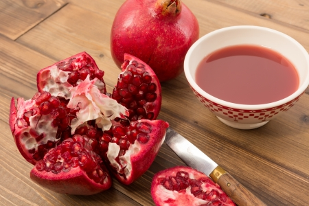 tannins: Cut pomegranate on a wooden table with bowl of juice