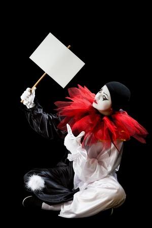 payaso: Pierrot joven sentado en un fondo negro con un signo vac�o