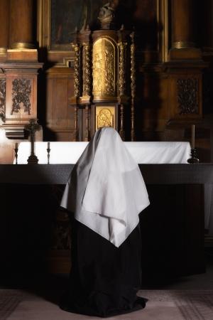 Nun bidden bij het altaar van een middeleeuwse 17e eeuwse kerk met tabernakel Stockfoto
