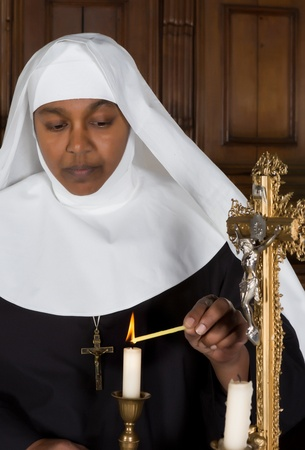 Mature nun lighting a candle on the altar of a medieval church photo