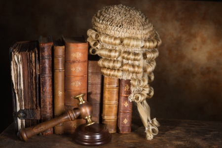 Antique judge's wig hanging on very old books photo