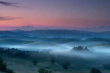 Toskana kurz vor dem Morgengrauen in San Quirico d'Orcia mit Blick auf Belvedere Haus in Dunkelheit und Nebel