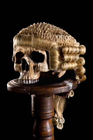 Antique horsehair judges wig on a creepy old skull Stock Photo