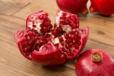 Closeup of two whole and one cut open pomegranates on a wooden table