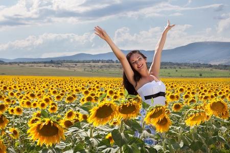 bulgaria: Joyful young woman being happy in a sunflower field in Bulgaria Stock Photo
