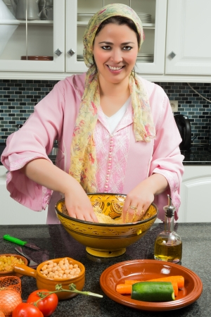 Traditional Moroccan immigrant woman in Europe cooking couscous during Ramadan in her modern kitchen