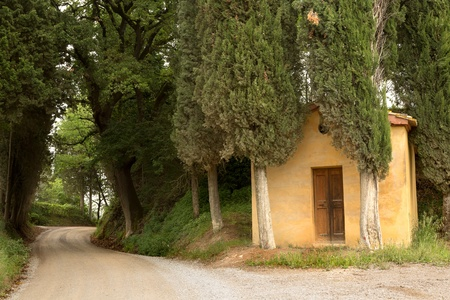 Little forest chapel and winding road in the hills of Tuscany near Pienza Stock Photo - 19656562