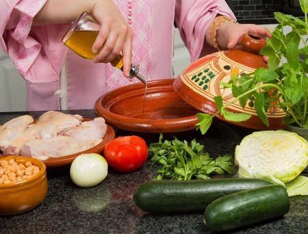 moroccan cuisine: Traditional Moroccan immigrant woman in Europe adding olive oil to her tajine during Ramadan in her modern kitchen Stock Photo