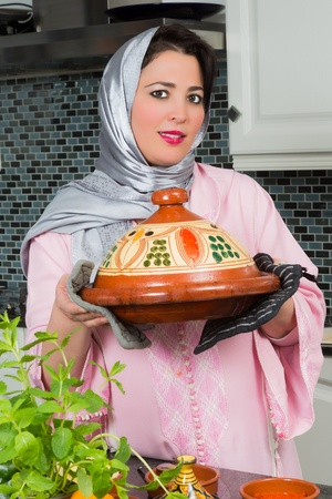 moroccan cuisine: Moroccan immigrant woman in Europe presenting her tajine dish during Ramadan in her modern kitchen