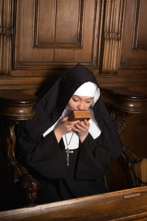 carmelite nun: Young nun kissing an old prayer book after praying (shot in a 17th century church interior)