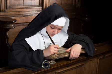nuns: Young nun writing in an ancient book in a medieval church interior