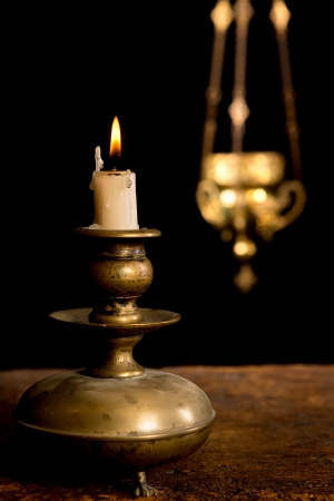 candle holders: Antique candlestick and burning candle and in the background a blurred incense holder