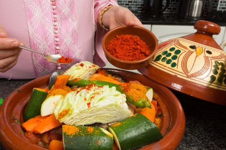 Traditional Moroccan immigrant woman in Europe adding spices to her tajine during Ramadan in her modern kitchen photo