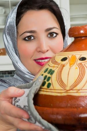 moroccan cuisine: Traditional Moroccan immigrant woman in Europe cooking tajine during Ramadan in her modern kitchen