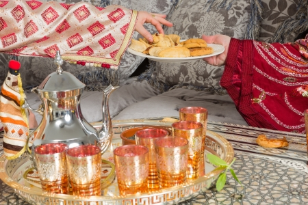Traditional Moroccan immigrant women presenting typical Ramadan cookies and tea photo