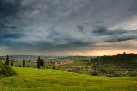 monticchiello: Walls and towers of the town of Monticchiello in Tuscany Italy during a rainstorm at sunset Stock Photo